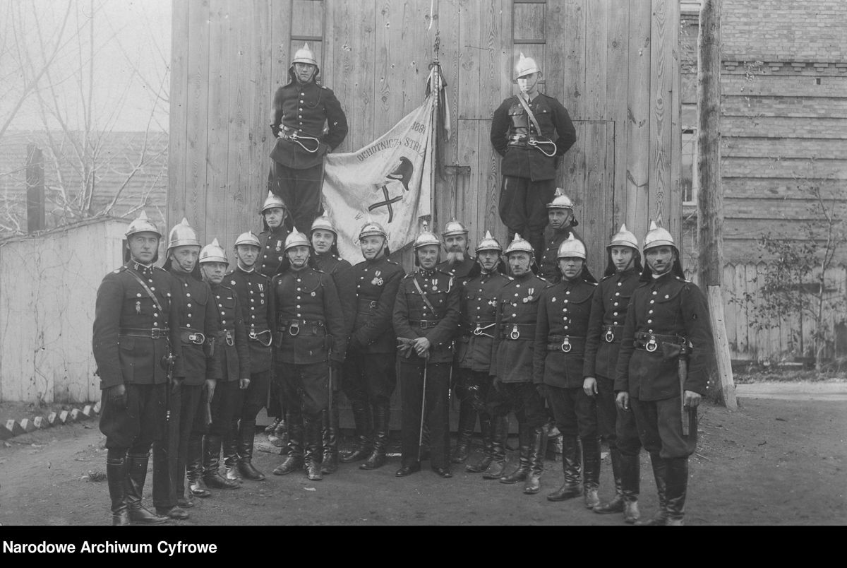 Jubileusz pięćdziesięciolecia Ochotniczej Straży Pożarnej w Równem. Fotografia grupowa najstarszych członków równieńskiej Ochotniczej Straży Pożarnej przed remizą, data nieznana.