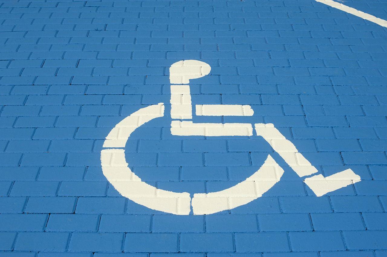 zdjęcie miejsca parkinkowego dla osób z niepełnosprawnościami: na niebieskim tle biały rysunek wózka inwalidzkiego