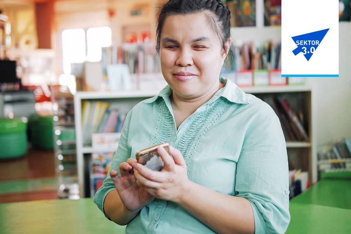 Uśmiechnięta niewidoma młoda kobieta korzysta ze smartfona
