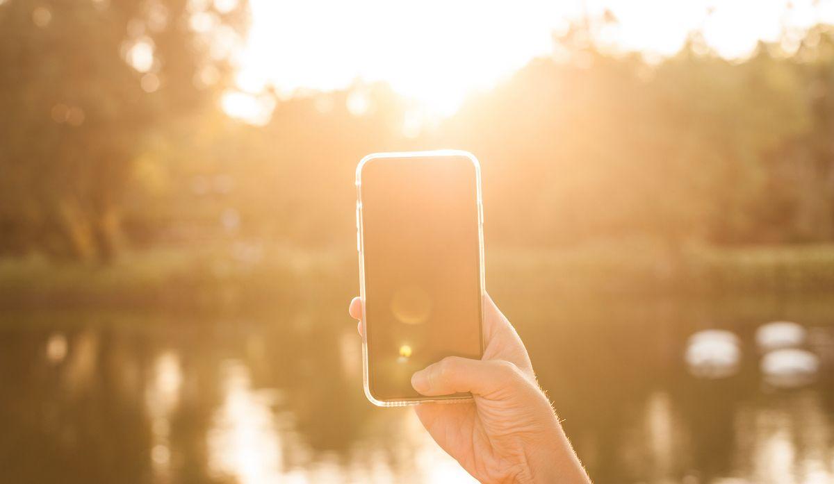 Ekran smartfona oglądany w słoneczny dzień. Słońce oślepia, na ekranie nic nie widać.